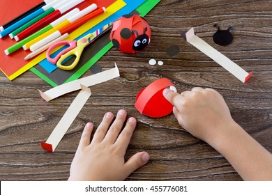The child holds a piece of paper and glues the of the handicrafts. The child makes crafts out of paper ladybug. Glue, paper, scissors on a wooden table. Children's art project, a craft for children.
