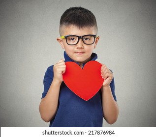 Child holds red heart, isolated grey wall background. Positive human emotions, feelings, attitude, life perception, face expressions. Compassion concept