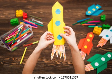 the child holds the rocket made of paper against the background of a wooden table. preschool Child in creativity in the home. Happy kid makes rockets from paper. Children's creativity.
