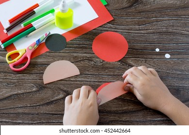 The child holds a sheet of paper and fold it in half. The child makes a postcard with ladybird. Glue, paper, scissors on a wooden table. Children's art project, a craft for children.