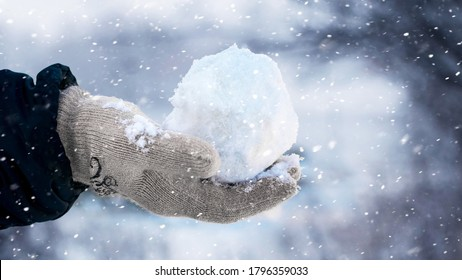 A child holds a snowball in his hand on the street during a snowfall