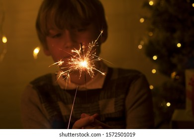 A child holds a sparkler, close-up. Sparkler and sparks macro photo festive background bokeh, magic atmosphere for Christmas and New Year