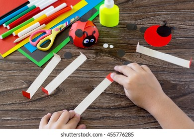 The child holds a strip of paper and fold it in half ends. The child makes crafts out of paper ladybug. Glue, paper, scissors on a wooden table. Children's art project, a craft for children.