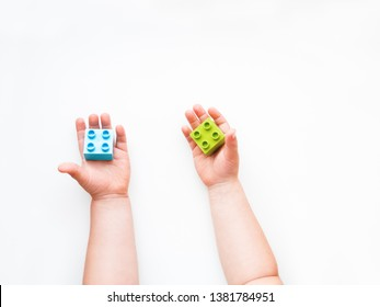 Child is holidng green and blue constructor blocks in fist. Kid's hands with bricks toy on white background. Educational toy, flat lay, top view.