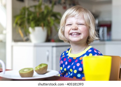 Child at home eating in kitchen