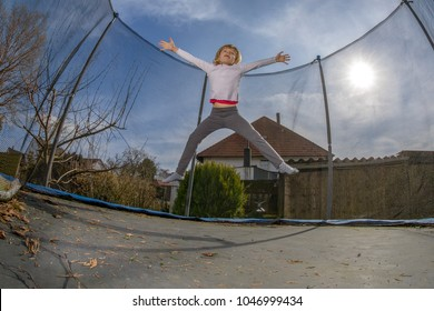 child at home in the garden jumping on a trampoline