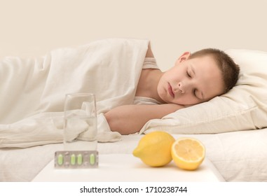 the child at home lies sick under a blanket with a temperature close-up with lemon and medicine