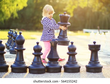 Child with huge chess figures outdoor