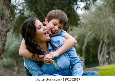 Child hugging his mother smiling on an autumn afternoon in the park