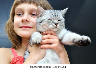 child hugging a young Scottish fold cat