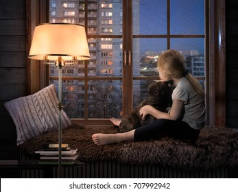 child hugs the dog and staring out the window. Rain, night city, water drops on glass. Cozy room, light floor lamp