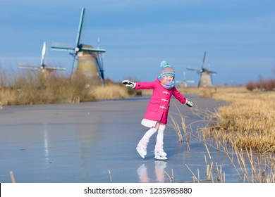 Child ice skating on frozen canal with wind mills and snow in Holland. Little girl with skates on natural ice on cold winter day in the Netherlands. Kids ice skate in snowy Dutch windmill landscape.