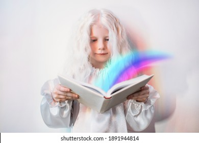 Child imagination. Story time. Fairytale magic. Portrait of curious sweet blonde little girl in white vintage dress with bright rainbow flowing from open book on light background.