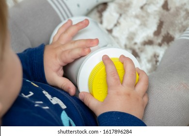 A child independently tries to open a plastic bottle of medicine, close-up. Child-resistant, childproof or CR packaging. Push&Turn Cap. Child safety concept