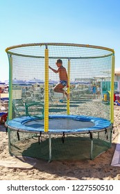 Child jump, run, trampolining in Open Jump Trampoline. Big Trampoline on the beach of Adriatic coast, Italy. Outdoor Trampoline with safety net with Zipper entrance.