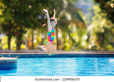 Child jumping and diving in swimming pool. Kids swim, jump and dive. Colorful rainbow swim wear for young kids. Little girl having fun on family summer vacation in tropical resort. Beach and water fun
