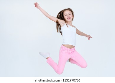 child jumping high in the air. aireness lightness freedom happiness and carefree childhood emotion concept. little girl on white background