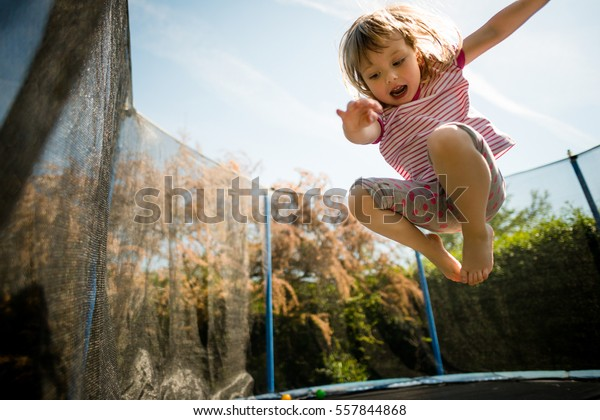 Child jumping high on big trampoline outside in garden
