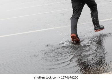 A child is jumping with rain boots in a large puddle after the rain in the spring season. The child's galoshes splash in the wet rain puddle creating a ripple in the water. Splashing and jumping