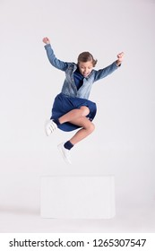 The child jumps from the cube in the studio.
