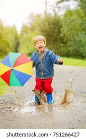 Child jumps on puddles in boots. Baby in the rain. A boy with a rainbow umbrella is walking outside. Autumn, vacation