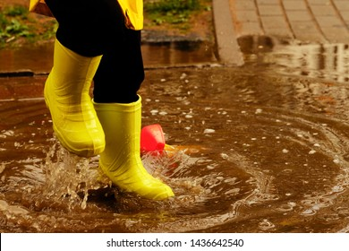 child jumps in a puddle arranges a storm for a small plastic boat. legs in yellow rubber boots.