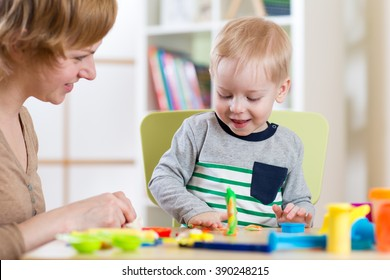 child kid boy and woman playing colorful clay toy at nursery or kindergarten