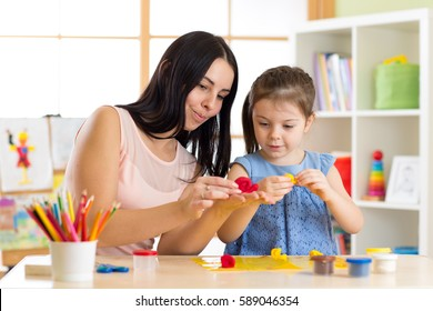 child kid girl and mother playing colorful clay toys at nursery at home