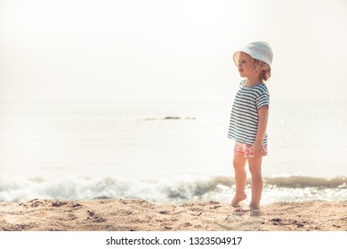 Child kid girl on beach looking into the distance searching for something with bright sunlight concept happy childhood lifestyle