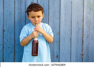 Child kid little boy drinking lemonade drink outdoor outdoors outside bottle