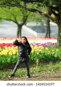 Child kid puckering up for a kiss happily and holding hand up with two fingers standing in tulip flower field. Little asian girl in black leather jacket and skirt with gray wool hat.