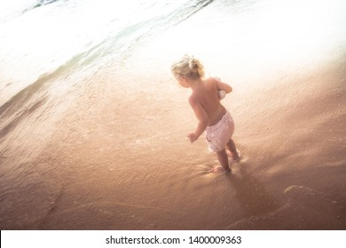 Child kid standing hesitated on beach in front of sea and going to swim concept children overcoming fear water