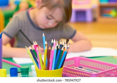 A child in a kindergarten draws at a desk