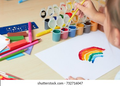 Child in kindergarten draws picture with paints