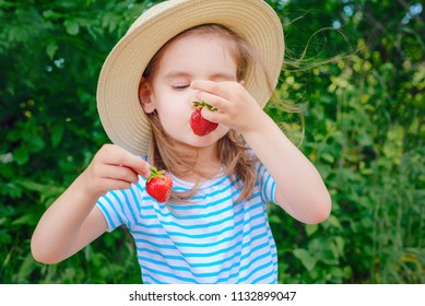 child is kissing a red strawberry.   concept of a healthy lifestyle.