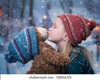 Child is kissing a Teddy bear under the falling snow. The concept of Christmas, children's happiness, love and confidence