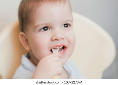 child in the kitchen eating fruit puree