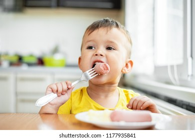 child in the kitchen eating sausage and mashed potatoes