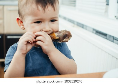The child in the kitchen hands greedily eating chicken, ham sitting at the table