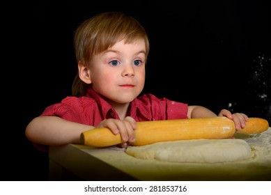 The child knead the flour, the dough with a rolling pin rolls. On a black background
