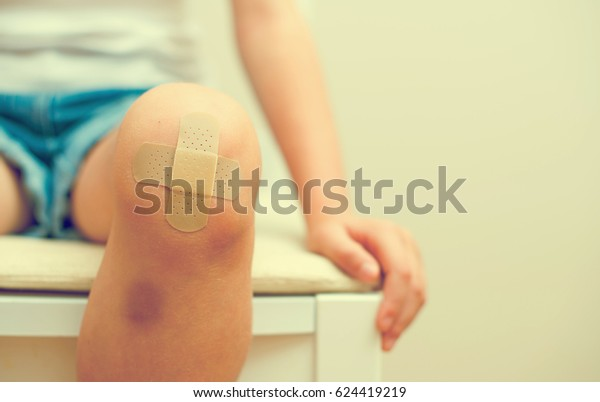 Child knee with an adhesive bandage and bruise.