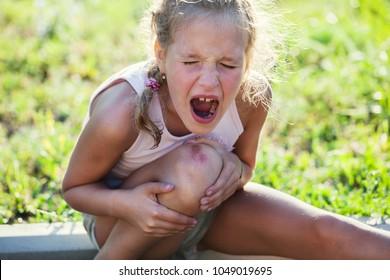 Child knee injury. Crying girl