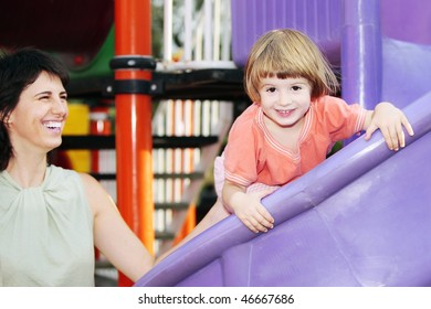 Child laughing in amusement park with under supervision of teacher or mother during the day