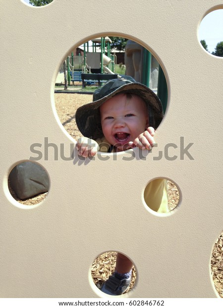 Child laughing and playing Peekaboo at the Playground on a sunny day.