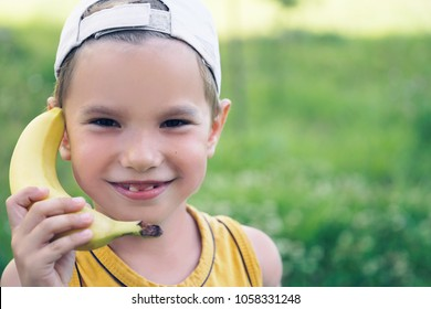 Child laughing while playing pretend with a wooden banana phone