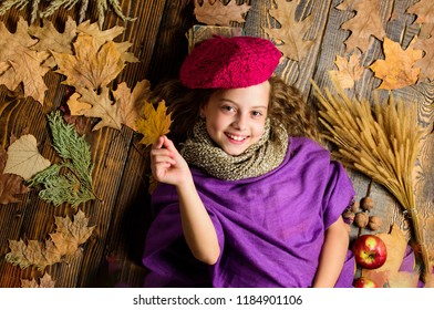 Child lay wooden background fallen leaves top view. Knitted accessory fashion detail. Fashion kid girl wear knitted hat beret and scarf. Autumn fashion accessories concept. Fashion trend fall season.