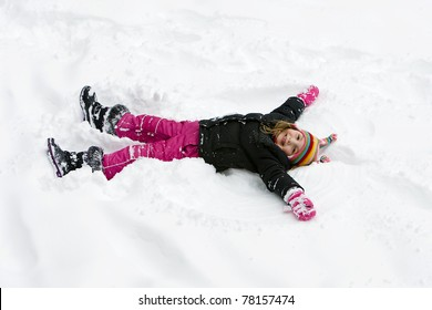 child laying down in the snow