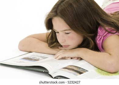 Child laying on a white background and reading a book