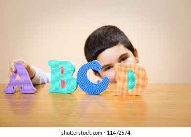 child learning the ABC's. The focus is on the letter D. Some copy space
