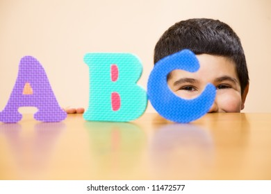 child learning the ABC's. The focus is on the his eyes